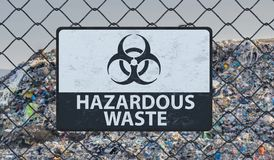 3D rendered illustration of hazardous waste sign on chain link fence. Landfill in background.  Royalty Free Stock Photography