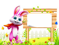 Pink easter bunny with carrot and big wooden sign. 3d rendered illustration of pink easter bunny with carrot and big wooden sign Stock Photos
