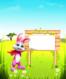 Pink easter bunny with carrot and sign on green grass. 3d rendered illustration of  pink easter bunny with carrot and sign on green grass Royalty Free Stock Image
