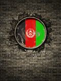 Old Afghanistan flag in brick wall. 3d rendering of an Afghanistan flag over a rusty metallic plate embedded on an old brick wall Stock Photos