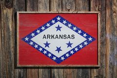 Wooden Arkansas flag. 3d rendering of an Arkansas State USA flag on a wooden frame and a wood wall Royalty Free Stock Images