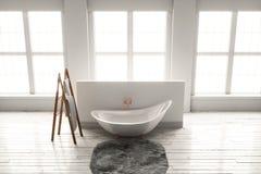 3D-rendering av ett badkar på ett trägolv framme av stora wi Fotografering för Bildbyråer