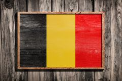 Wooden Belgium flag. 3d rendering of Belgium flag on a wooden frame over a planks wall stock photography