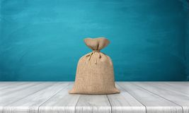3d rendering of a blank tied up hessian bag full of money standing on a wooden surface on blue background. Lottery win. Jack pot money. Cash bag Stock Photography