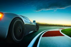 3D rendering of a brand-less grey sport car. With  motion blur . Race track background . Sunset scene Royalty Free Stock Photography