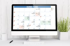 White workspace with computer calendar planner. 3d rendering calendar planner on computer. All screen graphics are made up royalty free stock images