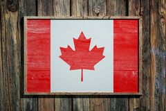 Wooden Canada flag. 3d rendering of Canada flag on a wooden frame over a planks wall Stock Images