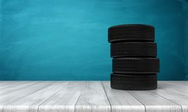 3d rendering of a car tires standing on a wooden surface in front of blue background. Spare wheels. Car service. Changing automobile parts Stock Photography