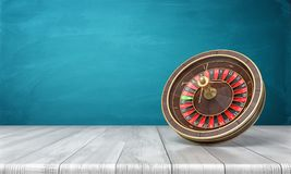 3d rendering of a casino roulette stands on its side on a wooden desk in front of a blue background. Stock Images
