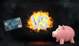 3d rendering of a concrete flaming letters VS stand between a credit card and a piggy bank. Choose banking services. Spend or save money. Investment vs Royalty Free Stock Image