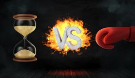 3d rendering of a concrete letters VS caught on fire between an hourglass and a red boxing glove. Time and effort. Time wasters. Fight for precious time Royalty Free Stock Photo