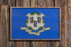 Wooden Connecticut flag. 3d rendering of a Connecticut State USA flag on a wooden frame and a wood wall Royalty Free Stock Image