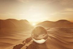 3d rendering of crystal ball on desert landscape with footsteps. In the evening sunlight Stock Image