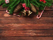 3D rendering dark christmas wooden background. With branches of fir, cones, bells and caramel canes Royalty Free Stock Photography