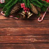 3D rendering dark christmas wooden background. With branches of fir, cones, bells and caramel canes Royalty Free Stock Photo