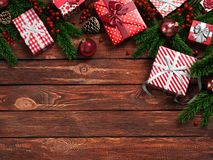 3D rendering dark christmas wooden background. With branches of spruce, holly berries, ornaments and gifts Stock Photos
