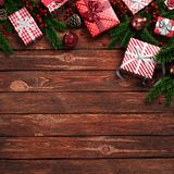 3D rendering dark christmas wooden background. With branches of spruce, holly berries, ornaments and gifts Stock Photo