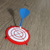 3D rendering dart on target. With wooden background and lens effect royalty free illustration
