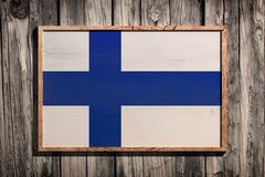Wooden Finland flag. 3d rendering of Finland flag on a wooden frame over a planks wall stock photo