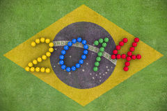 World Cup 2014. 3D rendering of footballs form in to the year 2014 over a Brazil flag painted on a grass field Stock Photography