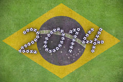 World Cup 2014. 3D rendering of footballs form in to the year 2014 over a painted grass field of Brazil Flag Royalty Free Stock Image