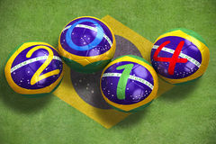 World Cup 2014. 3D rendering of footballs in the year 2014 on a grass field Royalty Free Stock Images