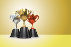 3D rendering gold, silver and bronze  awards winners cup sitting. On yellow tone background. Three cup trophies. Winners cup. Copy space on right side Royalty Free Stock Photos