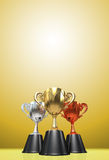 3D rendering gold, silver and bronze  awards winners cup sitting. On yellow tone background. Three cup trophies. Winners cup. Copy space on top Royalty Free Stock Photos