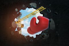 3d rendering of hoisting crane carrying red boxing glove and breaking black wall leaving hole in it with blue sky seen stock images