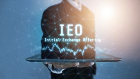 3D rendering of IEO text Initial Exchange Offering glowing hologram hover over tablet in business man`s hand and candle chart. stock photos