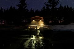 3d rendering of illuminated wooden log cabin behind frozen lake Stock Photo