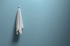 3D rendering : illustration of a piece of clean and white towel hanging on a blue pastel wall,light and shadow,copy space Stock Photo