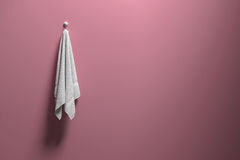 3D rendering : illustration of a piece of clean and white towel hanging on a pink pastel wall,light and shadow,copy space Stock Images