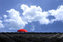 3D Rendering : illustration of Red umbrella floating above from the crowd of many black umbrellas against blue sky and clouds. Business leader concept, being Royalty Free Stock Images