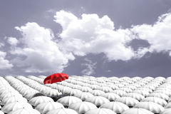 3D Rendering : illustration of Red umbrella floating above from the crowd of many white umbrellas against blue sky and clouds. Business leader concept, being Stock Photos