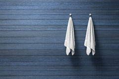 3D rendering : illustration of two piece of clean and white towel hanging on a wooden wall,light and shadow,copy space. 3d rendering,dark edges royalty free illustration
