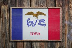 Wooden Iowa flag. 3d rendering of an Iowa State USA flag on a wooden frame and a wood wall Royalty Free Stock Photo
