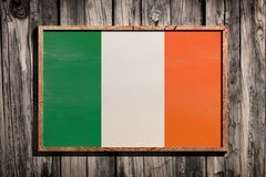 Wooden Ireland flag. 3d rendering of Ireland flag on a wooden frame over a planks wall stock photos