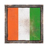 Old Ivory Coast flag. 3d rendering of an Ivory Coast flag over a rusty metallic plate wit a rusty frame. Isolated on white background Royalty Free Stock Photo