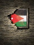 Old Jordan flag in brick wall. 3d rendering of a Jordan flag over a rusty metallic plate embedded on an old brick wall Royalty Free Stock Image