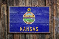 Wooden Kansas flag. 3d rendering of a Kansas State USA flag on a wooden frame and a wood wall Stock Images