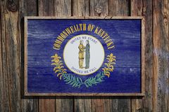 Wooden Kentucky flag. 3d rendering of a Kentucky State USA flag on a wooden frame and a wood wall Stock Image