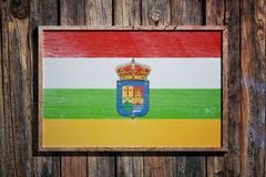 Wooden La Rioja flag. 3d rendering of a La Rioja flag on a wooden frame and a wood wall Royalty Free Stock Photo