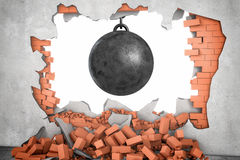 3d rendering of a large black wrecking ball hanging in a hole made in a brick wall with many bricks lying around. Royalty Free Stock Image