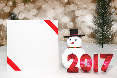 3D Rendering : 2017 light bokeh number and white card with red ribbon on perspective snowscape.snow man with sparkling bokeh wall. 3D Rendering : illustration of Stock Photos