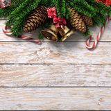 3D rendering light christmas wooden background. With branches of fir, cones, bells and caramel canes Stock Photography