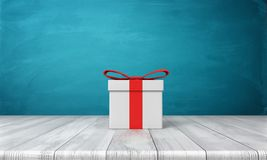 3d rendering of a lone white gift box with a red bow standing on a wooden desk in front of a blue background. Stock Photo
