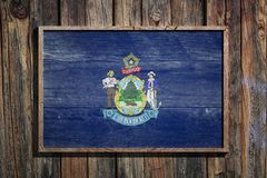 Wooden Maine flag. 3d rendering of a Maine State USA flag on a wooden frame and a wood wall Stock Photos