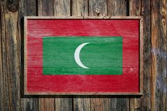 Wooden Maldives flag. 3d rendering of Maldives flag on a wooden frame over a planks wall Stock Images