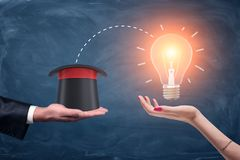 3d rendering of a male businessman`s hand holding a wizards hat and a female hand holding a bright glowing lamp. Royalty Free Stock Photography